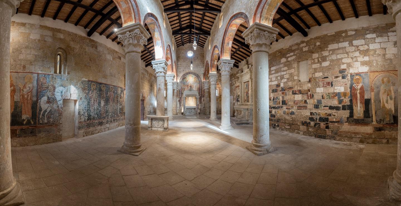 """Foto d'insieme degli affreschi della Chiesa abbaziale, in particolare si notano la """"parete-puzzle"""" sulla destra e la parete """"picchettata"""" sulla sinistra, fonte (c)FAI-Fondo Ambiente Italiano"""